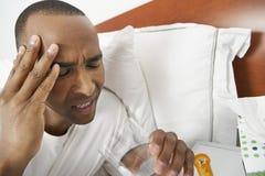 Mann mit den schweren Kopfschmerzen, die Pille einnehmen stockfoto