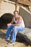 Mann mit den Tätowierungen, die auf einem Felsen sitzen Lizenzfreie Stockfotos