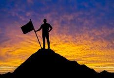 Mann mit der Flagge, die auf die Oberseite des Berges steht Lizenzfreie Stockfotografie