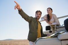 Mann mit der Frau, die mit weg vom Straßenfahrzeug zeigt Stockbild