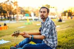 Mann mit der Gitarre auf dem Gras Lizenzfreie Stockfotografie
