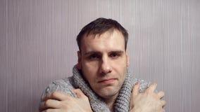Mann mit der grauen Strickjacke, zitternd von der Kälte und zu Hause husten auf Wandhintergrund stock footage