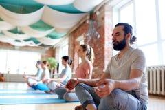 Mann mit der Gruppe von Personen, die am Yogastudio meditiert stockfotografie