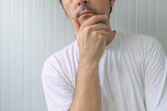Mann mit der Hand auf Kinn tiefe Gedanken denkend Lizenzfreie Stockfotos