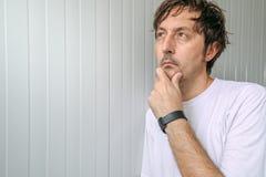 Mann mit der Hand auf Kinn tiefe Gedanken denkend Stockbild