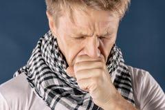 Mann mit der Kälte- und Grippekrankheit, die unter Kopfschmerzen und einem Husten leidet Hintergrund für eine Einladungskarte ode stockfotografie
