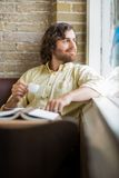 Mann mit der Kaffeetasse, die durch Fenster im Café schaut Lizenzfreie Stockfotos