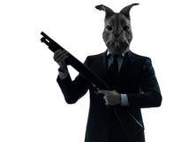 Mann mit der Kaninchenmaskenjagd mit Schrotflintenschattenbildporträt Stockfotografie