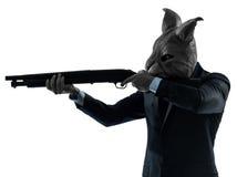 Mann mit der Kaninchenmaskenjagd mit Schrotflinteschattenbildporträt Stockfoto