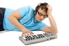 Mann mit der Midi-Tastatur- und Kopfhörer-Stellung Stockbilder