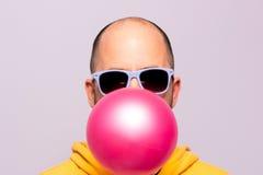 Mann mit der purpurroten Sonnenbrille, die rosa Kaugummi durchbrennt und die Kamera gegenüberstellt Stockbild