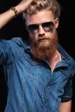 Mann mit der tragenden Sonnenbrille des langen roten Bartes, sein Haar reparierend Stockbilder
