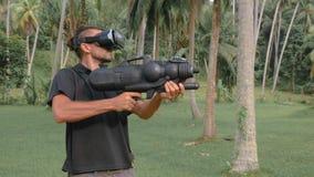 Mann mit der Waffe, die Spiel der virtuellen Realität im Dschungel spielt stock footage