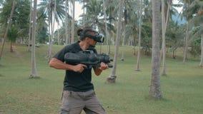 Mann mit der Waffe, die Spiel der virtuellen Realität im Dschungel spielt stock video