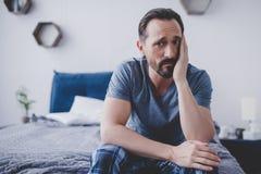Mann mit der Zahnschmerzen, die auf Bett sitzt stockfotografie
