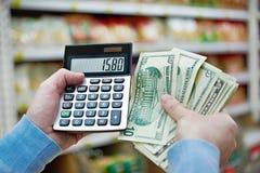 Mann mit Dollar und Taschenrechner betrachtet Kosten im Speicher Lizenzfreies Stockbild