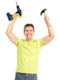 Mann mit drahtlosem Bohrgerät und Hammer lizenzfreie stockbilder