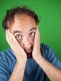 Mann mit dreißig Jährigen, der sein Gesicht im Schock hält Lizenzfreies Stockbild