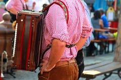 Mann mit einem Akkordeon, einem roten karierten Hemd und einem bayerischen Leder stockbilder
