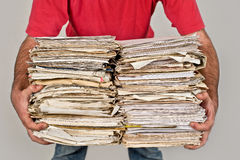 Mann mit einem Bündel alten Zeitungen in den Händen Lizenzfreies Stockbild