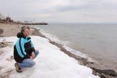 Mann mit einem Bart, der auf der Bank des Sees in bewölktem d sitzt Stockbild