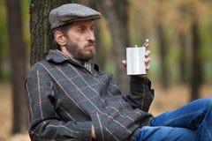 Mann mit einem Bart, der im Herbstwald mit einer Flasche in hallo sitzt Stockbilder