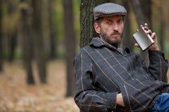 Mann mit einem Bart, der im Herbstwald mit einer Flasche in hallo sitzt Lizenzfreies Stockbild