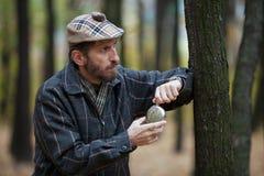 Mann mit einem Bart in der schottischen Kappe öffnet die runde Flasche Stockfotografie
