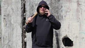 Mann mit einem Baseballschläger, der am intelligenten Telefon spricht stock footage