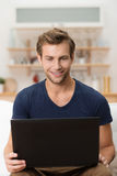 Mann mit einem begeisterten Lächeln unter Verwendung eines Laptops Lizenzfreies Stockbild