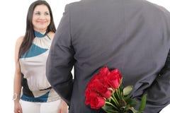 Mann mit einem Blumenstrauß von den roten Rosen, die seine Frau aufpassen stockfotos