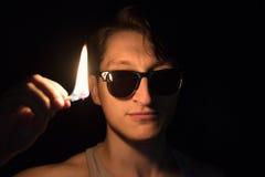 Mann mit einem brennenden Match in der Dunkelheit Untersuchung Kamera Stockbilder