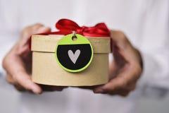 Mann mit einem Geschenk mit einem Herzen Lizenzfreies Stockfoto