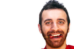 Mann mit einem glühenden Paprikapfeffer in seinem Mund Lizenzfreies Stockfoto