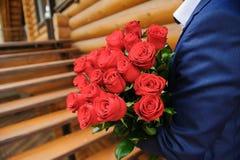 Mann mit einem großen Blumenstrauß von Rosen Stockbild