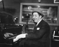 Mann mit einem großen Lächeln und einer Zigarre in seinem Mund, der das Klavier spielt (alle dargestellten Personen sind nicht lä Lizenzfreie Stockbilder