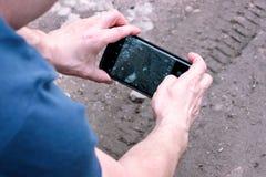 Mann mit einem Handy in seinen Händen macht ein Foto des Fahrrades, Auto, Automobilreifenbahnen auf schlammiger Spur Lizenzfreies Stockbild