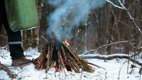 Mann mit einem Kanister nahe großem Lagerfeuer in der Winterwaldnahaufnahme stock video