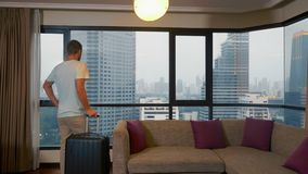 Mann mit einem Koffer auf dem Hintergrund von Wolkenkratzern in einem panoramischen Fenster stock video footage