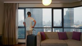 Mann mit einem Koffer auf dem Hintergrund von Wolkenkratzern in einem panoramischen Fenster stock video