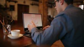 Mann mit einem Laptop, der durch ein ransomware Spywarevirus angesteckt wird, das um Geld bittet, die verschlüsselten Dateien zur stock video footage