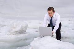 Mann mit einem Laptop in der schneebedeckten Umgebung stockfotografie