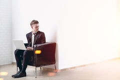 Mann mit einem Laptop in einem weißen Büro Lizenzfreies Stockfoto