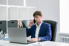 Mann mit einem Laptop im Büro Lizenzfreie Stockbilder
