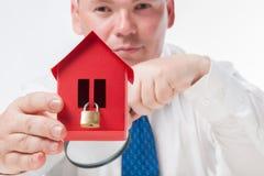 Mann mit einem Lupen- und Papierhaus Lizenzfreie Stockbilder