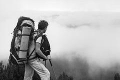 Mann mit einem Rucksack, der in den Bergen, über den Wolken steht Stockbilder