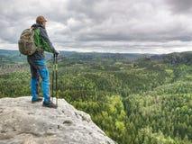 Mann mit einem Rucksack und Laufschuhstände auf einen Felsen lizenzfreies stockfoto