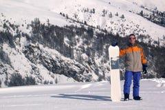 Mann mit einem Snowboard Stockfotografie
