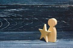 Mann mit einem Stern auf einem schwarzen Hintergrund Die Person empfing einen Ausweis der Unterscheidung Erhöhen Sie sich des Bei Stockbild