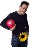 Mann mit einer Blume, die eine Kugel anhält Lizenzfreie Stockfotografie